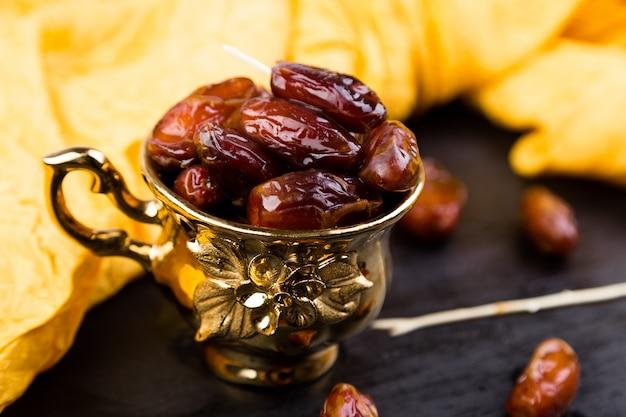 Fechas de frutos secos en copa de oro cerca del corazón negro pizarra.