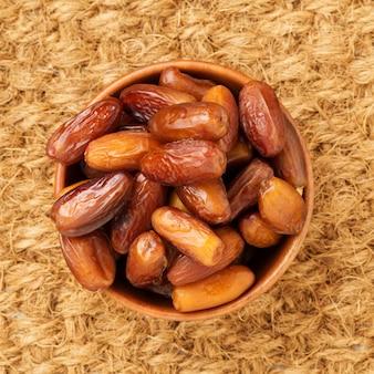 Fechas, frutos secos en cuenco de madera. comida tradicional de medio oriente, norte de áfrica.