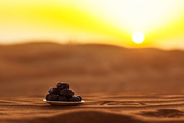 Fechas en un hermoso plato en el desierto en una hermosa puesta de sol, que simboliza el ramadán