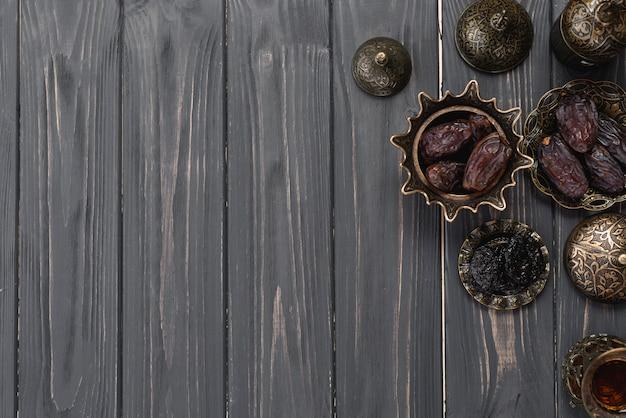 Fechas jugosas en el cuenco metálico árabe turco en tablón de madera