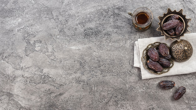 Fechas maduras jugosas y vaso de té sobre fondo de hormigón