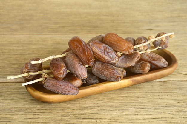 Las fechas secadas dan fruto en la bandeja de madera en la tabla de madera vieja.