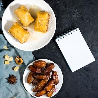 Fechas secas de frutas con dulces orientales y bloc de notas.