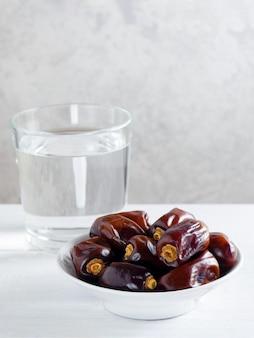 Fechas secas y un vaso de agua en la mesa blanca - ramadán, comida iftar.