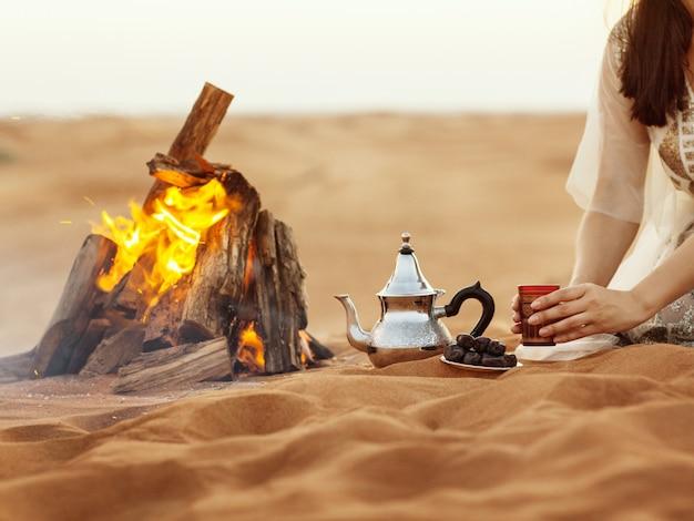 Fechas, tetera, taza con té cerca del fuego en el desierto con un hermoso fondo