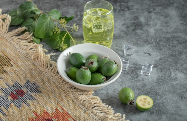 Feijoa fresca y vaso de limonada en mesa de mármol