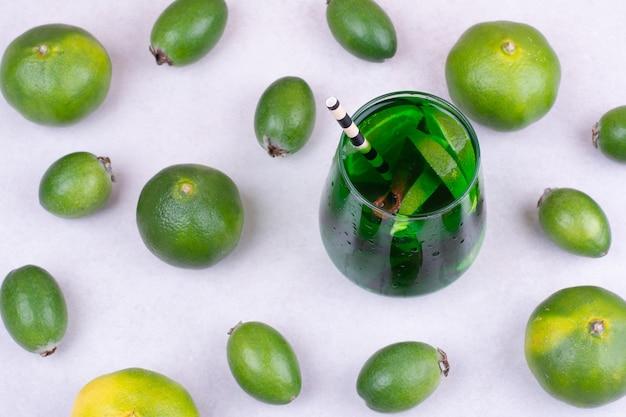 Feijoa y mandarinas con un vaso de jugo verde.