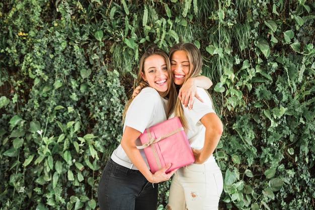 Felices amigas con caja de regalo rosa de pie delante de hojas verdes
