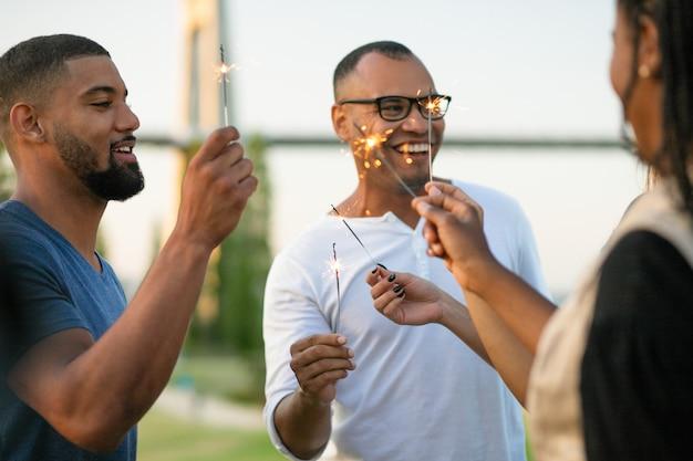 Felices amigos multiétnicos con bengalas