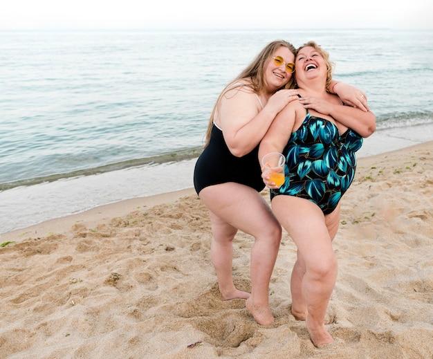 Felices amigos de talla grande de pie en la arena