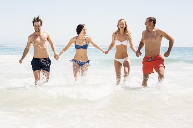 Felices amigos tomados de la mano y corriendo en la playa