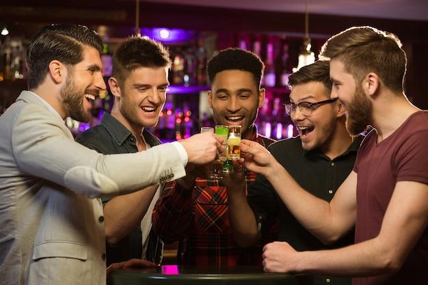 Felices amigos varones bebiendo cerveza y tintineo de vasos