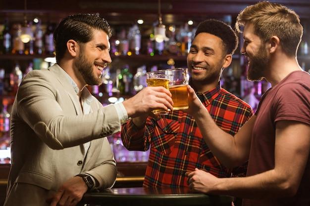 Felices amigos varones sonrientes tintinean con jarras de cerveza