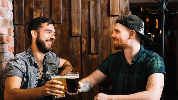 Felices amigos varones tostado vaso de bebidas alcohólicas