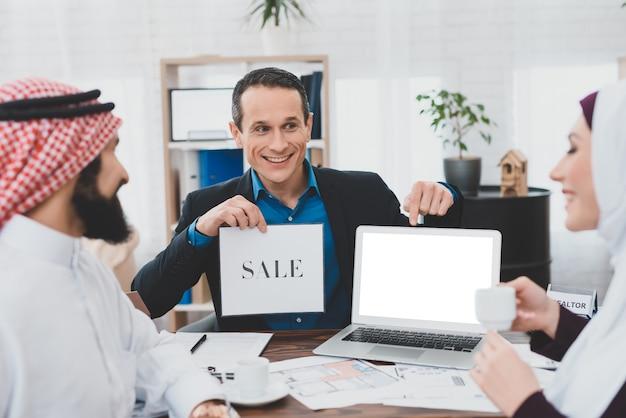 Felices árabes saudíes y corredor de seguros en la oficina