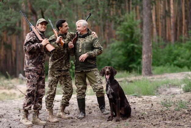Felices cazadores padre e hijos se están riendo.