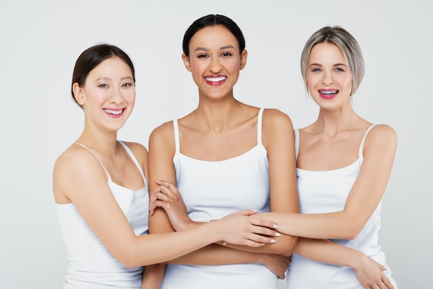 Felices chicas asiáticas, caucásicas y africanas con diferentes tipos de piel en bragas blancas y camisa.
