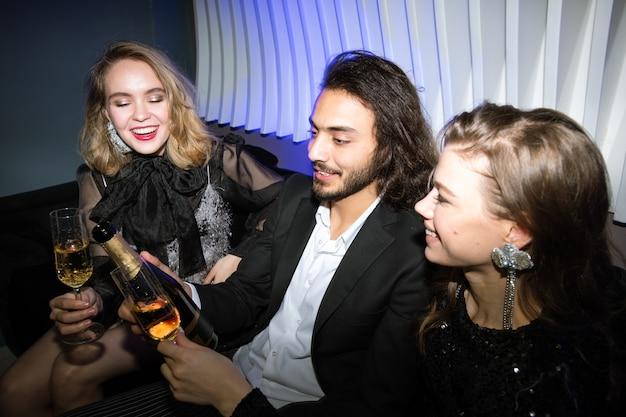 Felices chicas glamorosas con flautas de champán y joven sosteniendo una botella mientras está sentado en el sofá en el club nocturno y disfruta de la fiesta