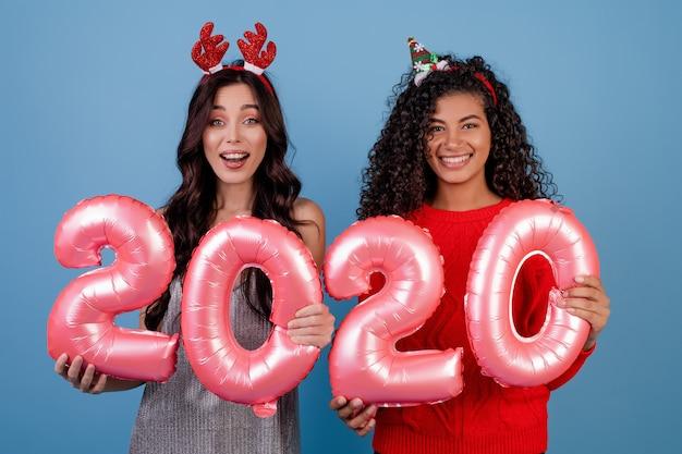 Felices chicas multirraciales con globos de año nuevo 2020 y divertidos aros festivos aislados en azul