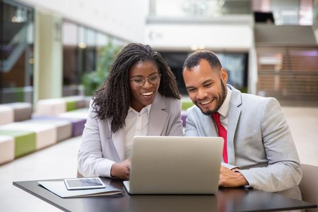 Felices colegas emocionados usando laptop para videollamada