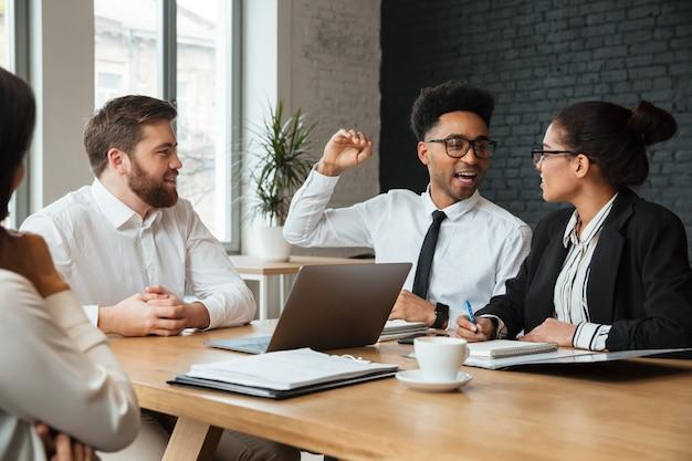Felices colegas jóvenes en el interior coworking