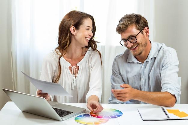 Felices colegas masculinos y femeninos discutiendo muestras de color en la oficina creativa