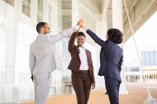 Felices colegas de negocios alegres celebrando el éxito