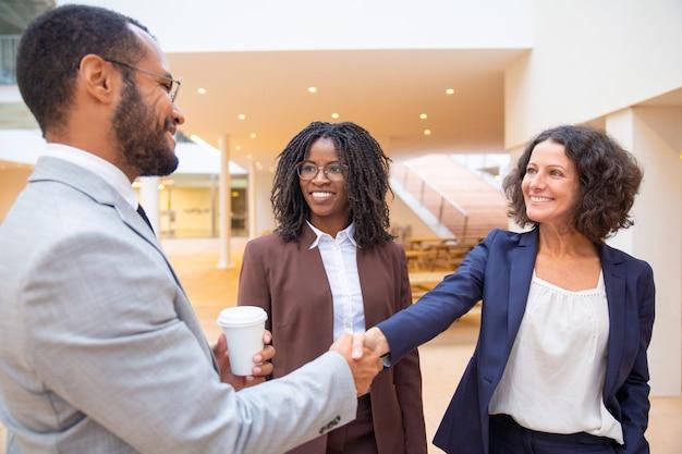 Felices colegas de negocios saludándose en el pasillo