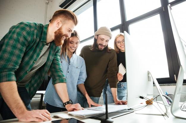 Felices colegas de pie en la oficina usando computadora