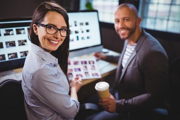 Felices colegas sentados en el escritorio de la computadora en la oficina creativa