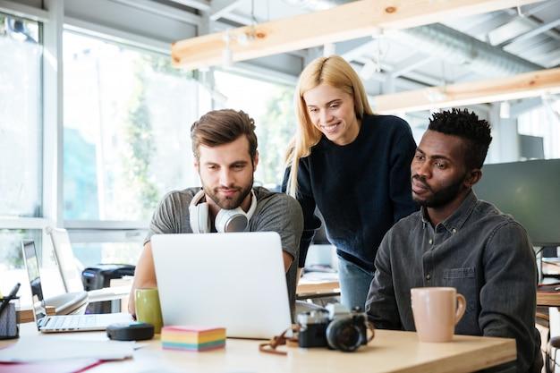 Felices colegas sentados en la oficina y coworking
