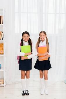 Felices colegialas multiétnicas de pie con libros de trabajo