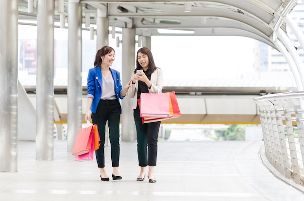 Felices compras asia mujeres con bolsas de compras.
