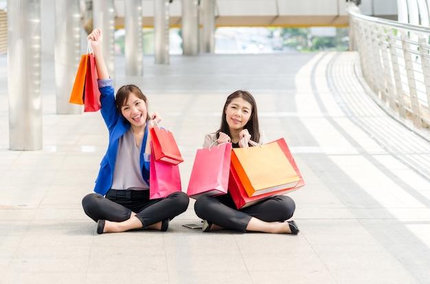 Felices compras mujeres con bolsas de la compra sentado al caminar.