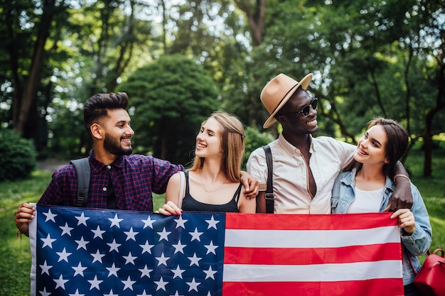 Felices cuatro estudiantes relajándose en la naturaleza con la bandera americana, celebrando el 4 de julio