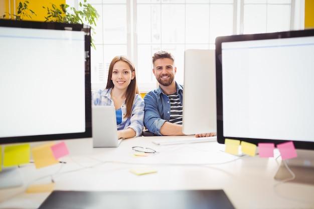 Felices diseñadores gráficos sentados en el escritorio