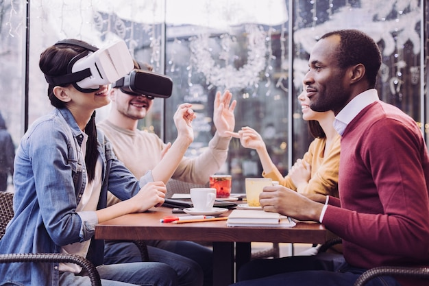 Felices dos amigos vigorosos que usan gafas de realidad virtual mientras sonríen y gesticulan
