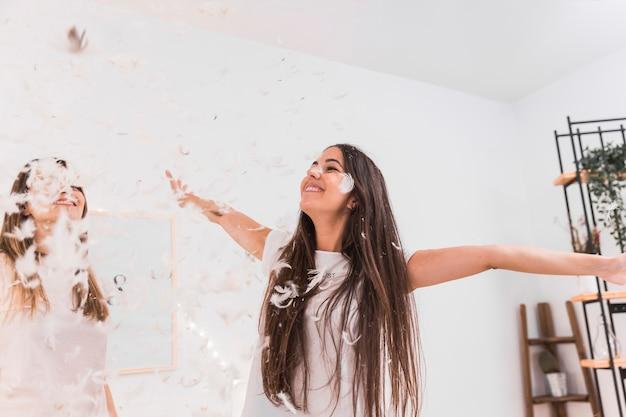 Felices dos mujeres bailando bajo la pluma blanca que cae