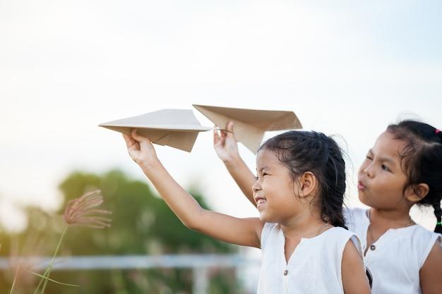 Felices dos niñas de niños asiáticos jugando con avión de papel de juguete juntos en el campo
