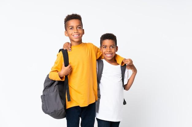 Felices dos niños estudiantes afroamericanos sobre blanco aislado