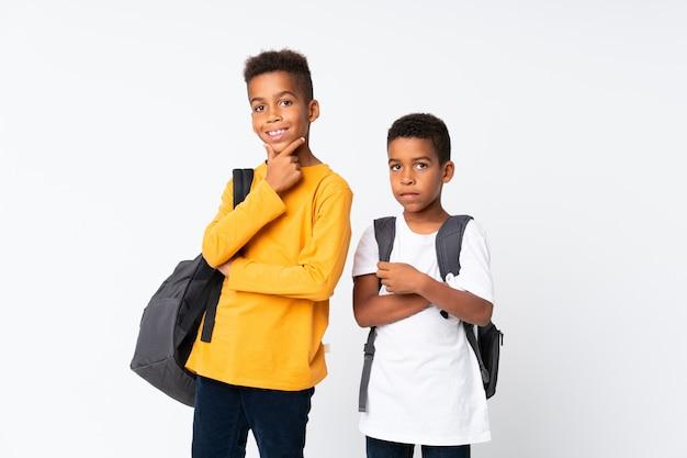 Felices dos niños estudiantes afroamericanos sobre pared blanca aislada