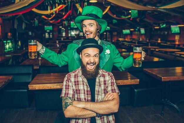 Felices y emocionados jóvenes están en pub y posan. el chico de enfrente mantiene las manos cruzadas y sonríe. joven detrás de llevar traje verde y tiene dos jarras de cerveza.
