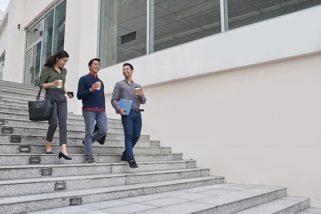 Felices empresarios asiáticos tomando un café saliendo del edificio de oficinas por un corto paseo marítimo