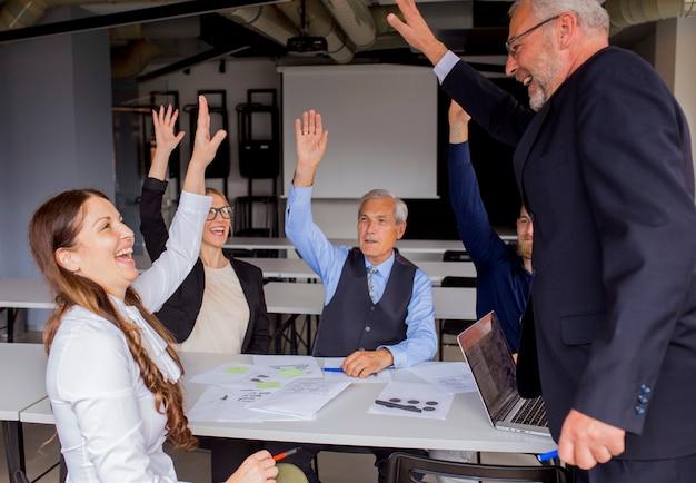 Felices empresarios exitosos levantando sus manos en la reunión del consejo