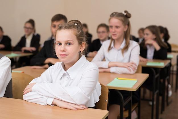 Felices escolares se sientan en un escritorio en el aula