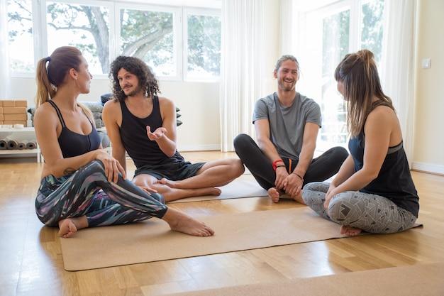 Felices estudiantes charlando después de la clase de yoga