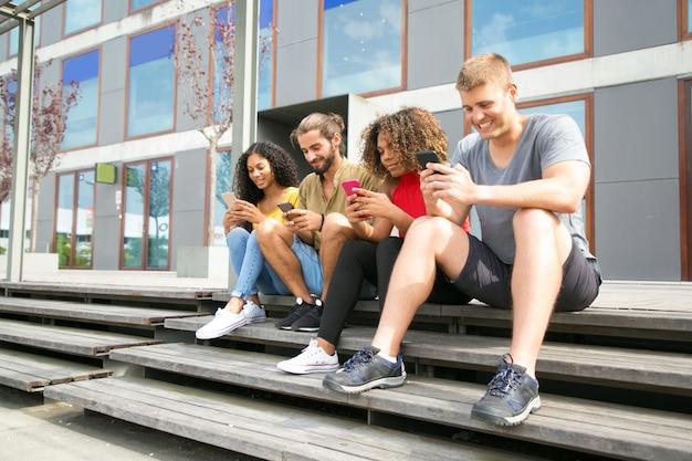 Felices estudiantes multiétnicos sentados juntos