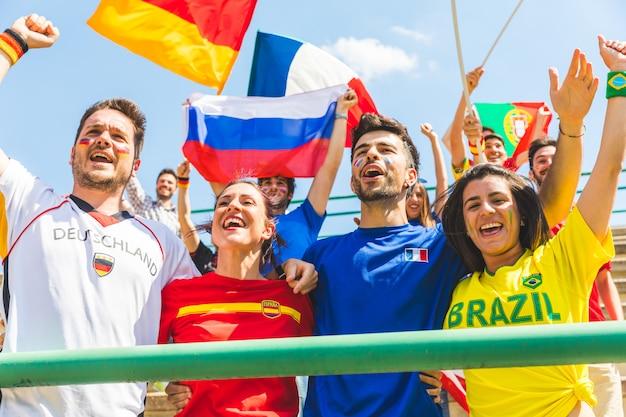Felices fanáticos partidarios de diferentes países juntos en el estadio