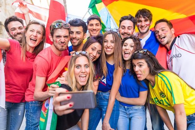 Felices fanáticos partidarios tomando un selfie todos juntos