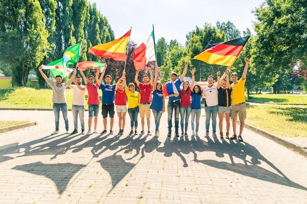 Felices fanáticos simpatizantes con banderas y camisetas multicolores.